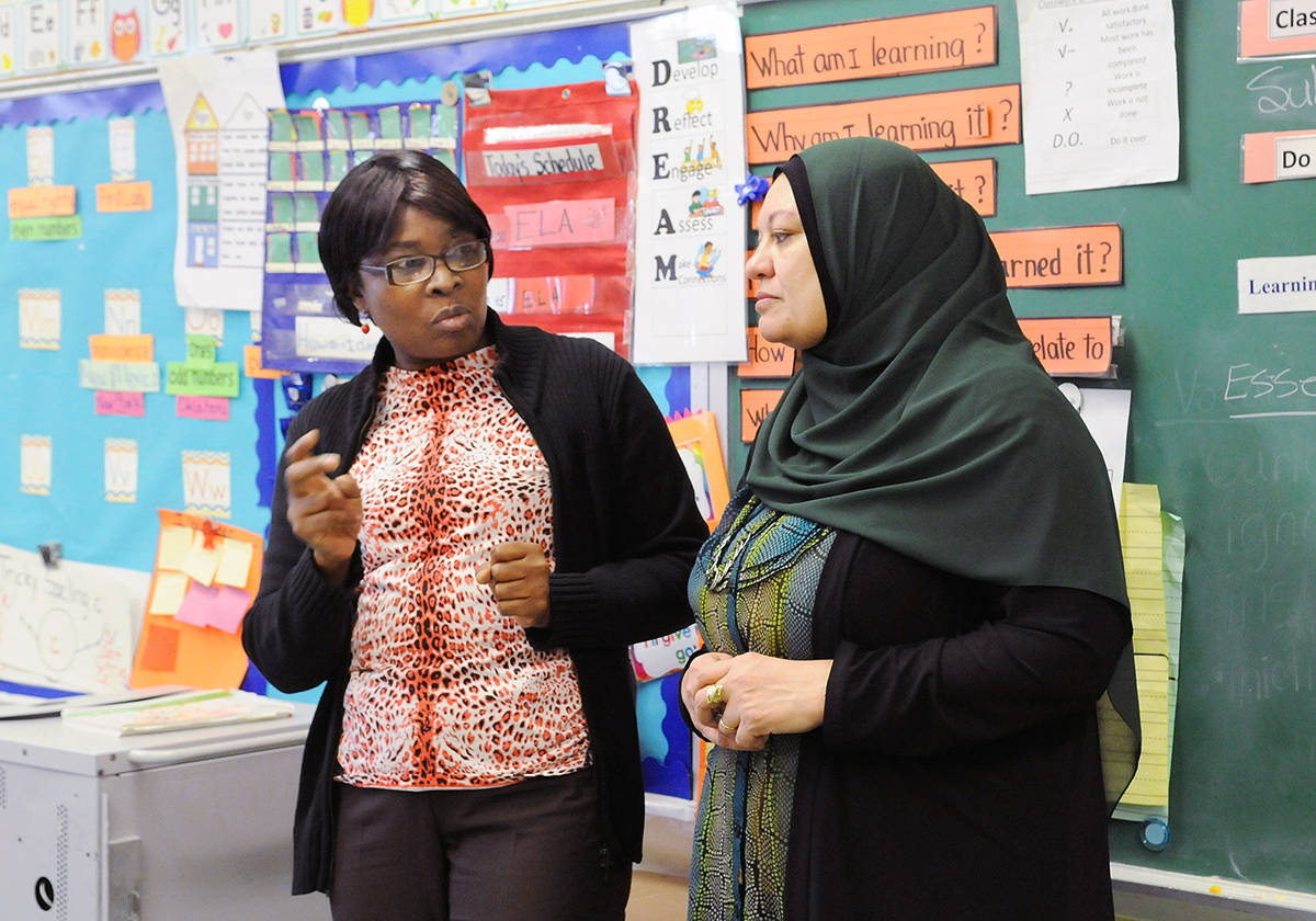 Teacher Guerda Plaisir (left) talks to literacy coach Tagrid Sihly in her 2nd-gr