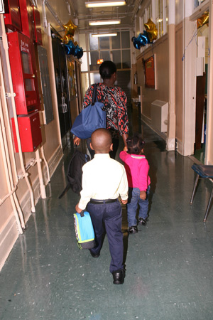 A kindergarten student follows his mother and little sister to his new class.
