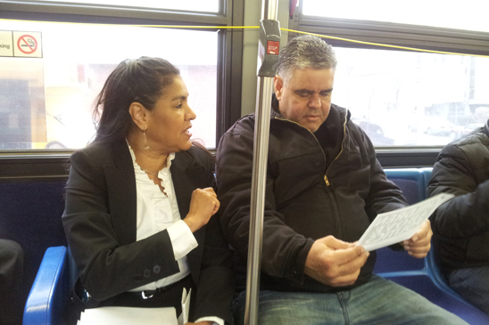 UFT District 6 Representative Mayra Cruz distributes leaflets on the #7 bus.