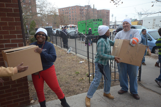UFT Vice President Janella Hinds (left), Brooklyn HS for Public Service secretary Sherma Owens and UFT President Michael Mulgrew are part of a chain delivering supplies. (Miller Photography)