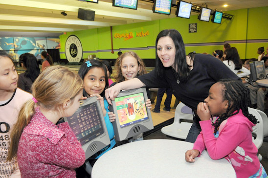 Third-grade teacher Bonnie Pitera and students check out the scoring terminal. (Jonathan Fickies)