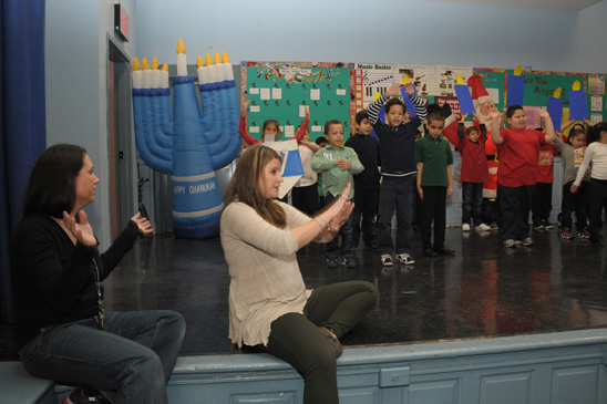 "Teachers (from left) Nicole Moskowitz and Lauren Rosenthal prompt kids during ""Hanukkah Ha Ha."" (Miller photography)"