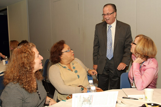 Welfare Fund Director Arthur Pepper (standing) chats with Danita Susi, a speech teacher at PS372 in District 75 in Brooklyn; Florence Bianco, a speech teacher at PS 151 in in Queens; and Virginia Hill, a speech teacher at the Teachers Center. (Miller Photography)