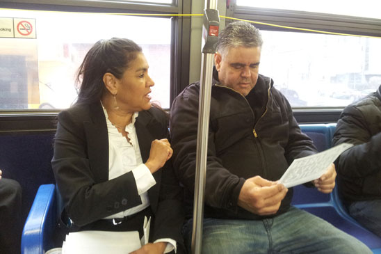 District Representative Myra Cruz talks to a commuter on the M7 bus about the need to reach a fair evaluation agreement.