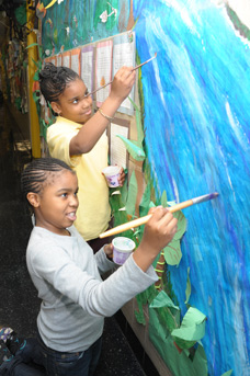 Students Tara and Jamilea are fully absorbed as they paint a river running throu