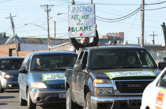 With signs fastened to cars and some held by members, vehicles are lined up as t