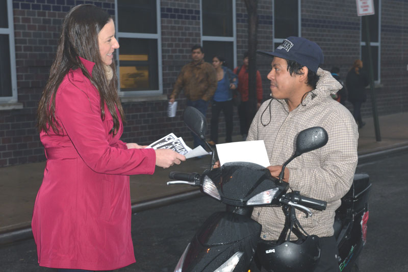 Jennifer Jaeger, a teacher at PS 239 in Queens, stops passer-by Louis Migar on his scooter to hand him a flier on a citywide Day of Action on Jan. 14.