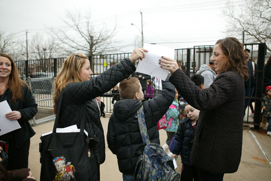 Third-grade teacher Stephanie Pascale hands a flier to a parent at PS 55 on Staten Island. (Bruce Cotler)
