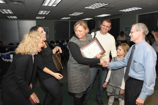 Award-winner Ganna Kazakova, a school nurse from PS 95, receives a handshake from Brooklyn Borough Representation Howard Schoor as (second from left) her schools chapter leader, Georgia Nikoloudakis, District 21 Representative Judy Gerowitz (far left) and her family share her happiness. (Miller Photography)