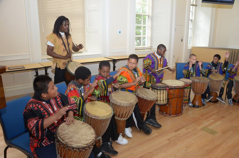 Spicing up the Brooklyn event are students playing African drums led by instruct