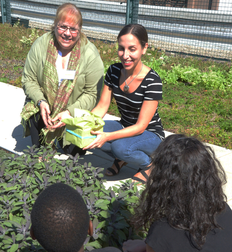 Susan Schenker and Maggie Monaco show students some plants.