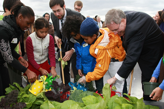 Students show state Daniel Squadron and Scott Stringer how to plant.