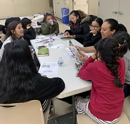 A woman reads to a group of children sitting at a table.