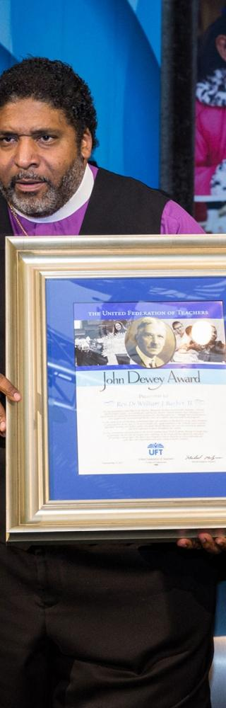 The Rev. Dr. William Barber II receives the John Dewey Award from Anthony Harmon