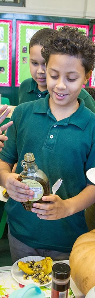 Students take turns dribbling maple syrup on an acorn dish