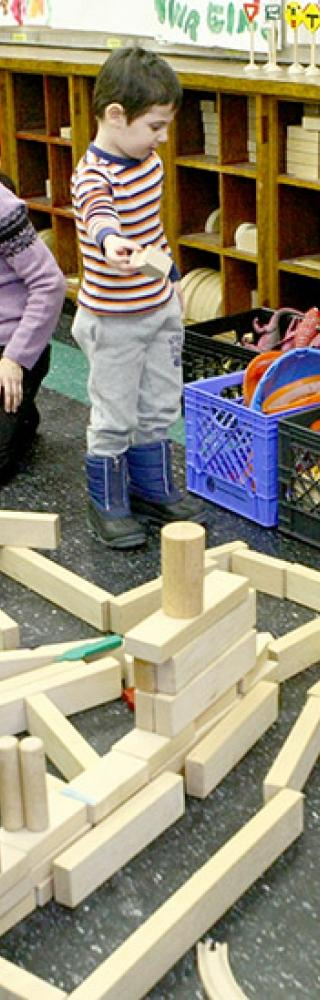 Students use blocks to build a cityscape under the watchful eye of pre-K teacher