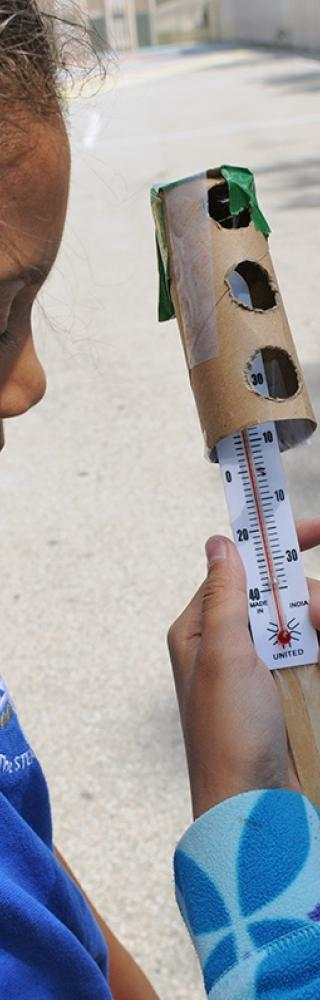 Students check the thermometer they have outfitted with a protective covering so
