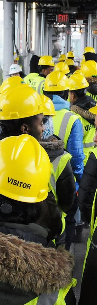Wearing hard hats and vests, students check out the view from the glass-enclosed