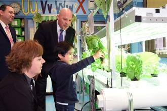 First-grader Rodrigo explains the school's hydroponic plant lab as visitors (inc