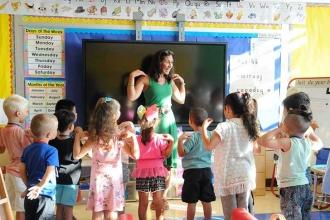 Woman in front of group of children in classroom with hands on shoulders