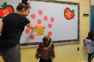 Woman and child pointing to bulletin board