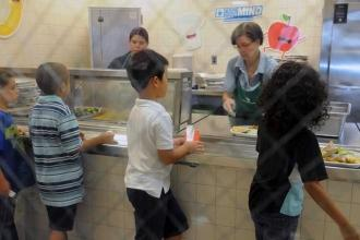 3 students standing in front of cafeteria trays