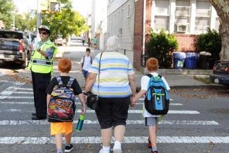 Woman holding hands of two boys wearing backpacks crosses street