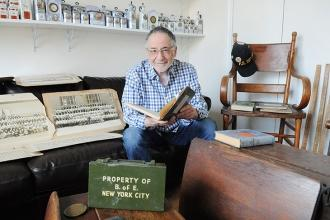 Marty Raskin sits among his treasures, including a Board of Education first-aid