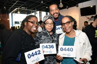 4 people smiling holding up running bib numbers