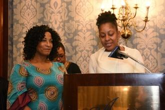 Two women standing at a podium while one of them speaks