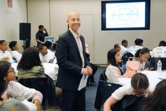Man standing in a room with children seated, smiles at the camera