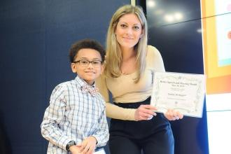 Woman holding plaque poses with boy