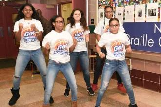 Students on the cheer team at Cardozo HS in Queens perform a cheer in front of t