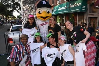 People wearing colorful hats pose with duck mascot wearing a NY Cyclones uniform