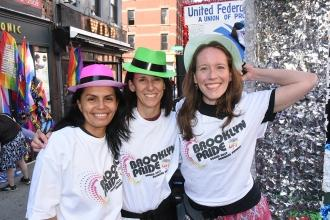 Three women wearing colorful hats