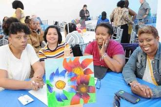"PS 36 members enjoy the event and the bright and beautiful ""flowers"" on their ta"