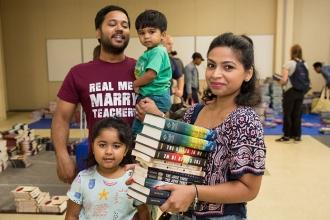 Proma Hassan, a teacher at MS 217 in Queens, stocks up on free books with her fa