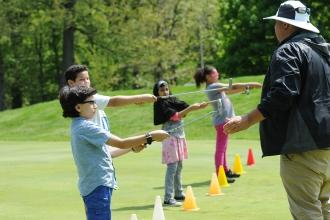 Boys and girls hold out golf club while instructor watches