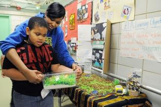 Kylah Hopkins helps a 3rd-grader present his grasslands habitat during the Galle