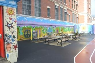 The PS 119 outdoor murals (above and at right) put a happy face on the 110-year-