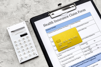 Health Insurance Claim Form on a clipboard with a calculator and credit card