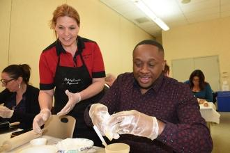 Chapter advocate Rashad Brown is guided by baking coach April Bier.