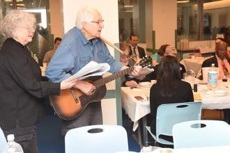 "George Altomare, a UFT founder, leads the singing of ""Dayenu"" with his friend, V"
