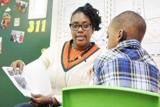 Lorge School teaching assistant Chantay Reid works with a student on reading in