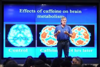 Man speaks with brain scans presentation behind him