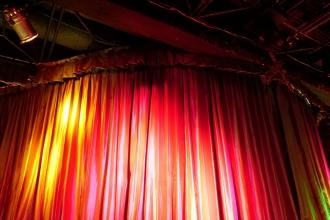 red stage curtain with light coming from the left