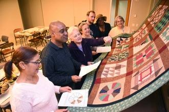 Stephanie Kollar (third from left), retired art teacher and creator of the quilt