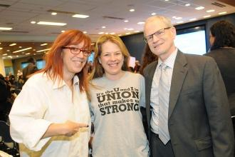 Two women and a man pose for photo displaying a grey t-shirt
