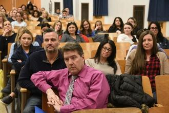 Staff members, including Chapter Leader Michael Sims (foreground), listen to the