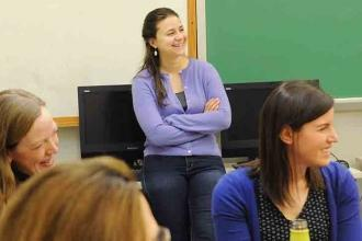 NYC iSchool teacher Victoria Moyer (standing) chuckles during a meeting at her s